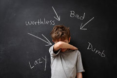Abusive words hurt. A young boy stands in front of a blackboard that has abusive words written on it Stock Image