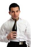 Abuso de álcool - vinho bebido do frasco da terra arrendada do homem foto de stock