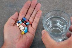 Abuso de tomar la medicina en una mano imagenes de archivo