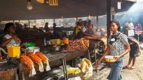 ABUYA, NIGERIA, ÁFRICA - 3 DE MARZO DE 2014: Mujeres africanas no identificadas que preparan los pescados y la otra comida en el  Imágenes de archivo libres de regalías