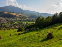Abwärts vom Berg zur Stadt überwältigt mit Gras Sush-Heu wird in einem Stapel verpackt Lizenzfreie Stockfotografie