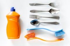 Abwaschflüssigkeit, -bürsten und -Geschirr auf Draufsicht des weißen Hintergrundes Lizenzfreies Stockfoto
