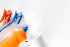 Abwaschflüssigkeit, -Geschirr und -bürsten auf weißem copyspace Draufsicht des Hintergrundes Lizenzfreies Stockfoto