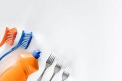 Abwaschflüssigkeit, -Geschirr und -bürsten auf weißem copyspace Draufsicht des Hintergrundes Stockfotos