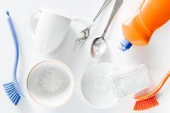 Abwaschflüssigkeit, -schwamm, -bürste und -Geschirr auf Draufsicht des weißen Hintergrundes Lizenzfreie Stockfotografie