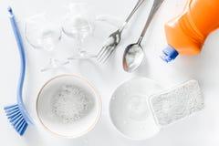 Abwaschflüssigkeit, -schwamm, -bürste und -Geschirr auf Draufsicht des weißen Hintergrundes Stockfotografie