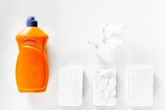 Abwaschflüssigkeit, -schwamm und -Geschirr auf Draufsicht des weißen Hintergrundes Stockbild