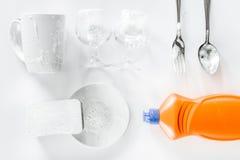 Abwaschflüssigkeit, -schwamm und -Geschirr auf Draufsicht des weißen Hintergrundes Stockfotografie