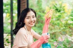 Abwaschflüssigkeit und -schwämme Nettes asiatisches Frauenreinigungsfenster Stockfoto