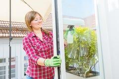 Abwaschflüssigkeit und -schwämme Reinigungsfenster der jungen Frau, Abschluss oben lizenzfreies stockfoto