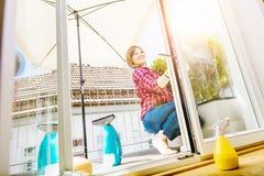 Abwaschflüssigkeit und -schwämme Reinigungsfenster der jungen Frau, Abschluss oben stockfotos