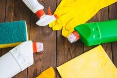 Abwaschflüssigkeit und -schwämme Sprays und Gummihandschuhe auf einem hölzernen backgroun Lizenzfreie Stockfotografie