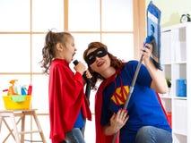Abwaschflüssigkeit und -schwämme Superheldfrau und -tochter, die Gitarre spielen und auf Reinigungsanlage singen Familie bereit z Stockbilder