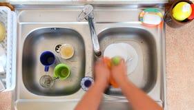 Abwaschschüsselperson, die das Spülbecken säubert Stockfoto
