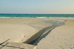 Abwasser auf goldenem Sandstrand mit blauem Ozean Stockfoto