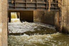 Abwasser, das vom StadtAbflussrohr fließt Stockfotografie