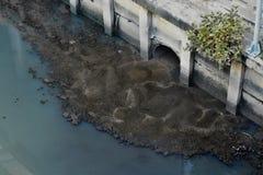 Abwasser von den Abflüssen in der Stadt auf Asiaten Stockfotos