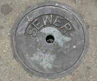 Abwasserkanal-Abflussrohr in der Straße Stockfotos