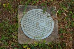 Abwasserkanalabdeckung das Gras Stockfotos