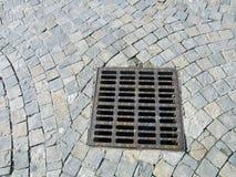 Abwasserkanalabdeckung an gepflastertem Stein Stockfotografie