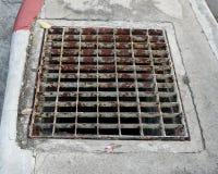 Abwasserkanalabfluß auf dem Fußweg Stockbilder