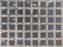 Abwasserkanaldeckel von achtundvierzig metallischen Quadraten für Hintergrund Stockfotografie
