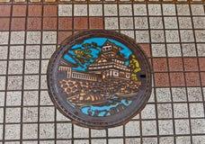Abwasserkanaleinsteigeloch mit Nakatsu-Schlossbild Lizenzfreie Stockfotografie