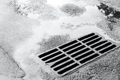 Abwasserkanalgitter auf nasser Straße mit Pfützen Lizenzfreie Stockfotos