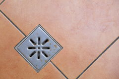 Abwasserkanalgitterabwasser auf Boden im Badezimmer Stockbilder