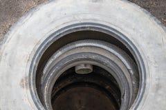 Abwasserkanalgrube mit Autoreifen stockfotos