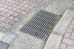 Abwasserkanalkanaldeckel in einer Stadtstraße Stockfotos