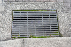 Abwasserkanalkanaldeckel in einer Stadtstraße Stockfotografie