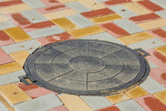 Abwasserkanalkanaldeckel umgeben durch eine Straße Stockbild