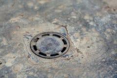 Abwasserkanalluke in der Straße in der Tageszeit Lizenzfreies Stockbild