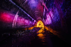 Abwasserkanaltunnel belichtet durch Farblaternen Stockbilder