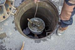 Abwasserkanalwartung, schauend hinunter das Einsteigeloch 2 Lizenzfreies Stockfoto