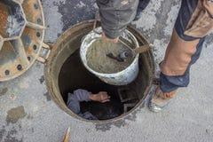 Abwasserkanalwartung, schauend hinunter das Einsteigeloch Stockbilder