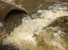 Abwasserlaufen langsam von einer konkreten Rohrleitung direkt auf einen natürlichen Teich mit grünem Gras auf der Bank und dem he Stockbilder