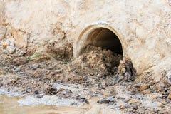 Abwasserleitung, die den Fluss verunreinigt Stockfotografie