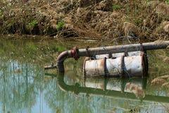 Abwasserleitung im See auf sich hin- und herbewegenden Fässern Stockfoto