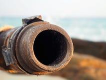 Abwasserleitung ist rostig und der Hintergrund ist das Meer Stockfotografie