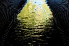 Abwasserrohr mit grünem Wasser Stockfotos