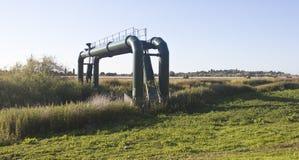 Abwasserrohre über einem Fluss Lizenzfreie Stockfotos