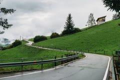 Abweichen der gefährlichen Straße auf einem Hügel während der nassen und ungünstigen Wetterbedingungen Stockbilder