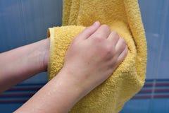 Abwischen übergibt ein gelbes Tuch Lizenzfreie Stockfotos