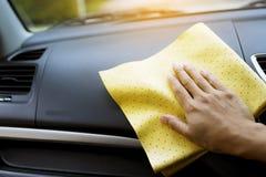 Abwischen des Autos mit einem gelben microfiber Stoff durch Hände Stockbild