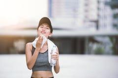 Abwischen des geschwitzten durstigen trainierenden weiblichen trinkenden Süßwassers nach der Ausbildung Lizenzfreies Stockbild