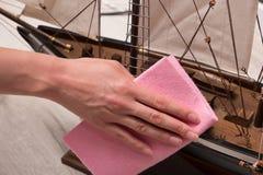 Abwischen des Staubes vom hölzernen Segelschiff Lizenzfreies Stockbild