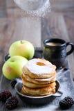 Abwischen mit Puderzucker über Apfelstückchen Stockfoto