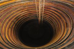 Abyss. Chains disappearing into a dark chamber with concentric circles opening wide at the top Stock Image
